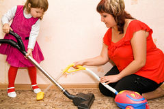 La niña y la mujer limpian una alfombra con la aspiradora imagen de archivo libre de regalías