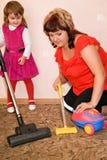 La niña y la mujer limpian una alfombra con la aspiradora fotografía de archivo