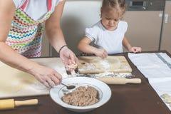La niña y la mamá hacen las bolas de masa hervida en la cocina en casa Foto de archivo libre de regalías