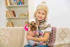 La niña y su animal doméstico se vistieron en ropa caliente Imagenes de archivo