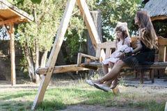 La niña y su madre se sientan en el banco y disfrutan de un beautif Imagen de archivo