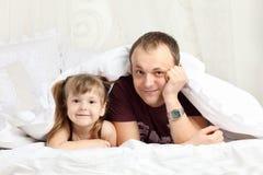 La niña y su padre miran hacia fuera de debajo la manta Foto de archivo