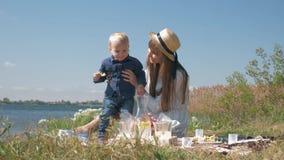 La niñez feliz, bebé divertido come el limón y jugar con la mamá joven durante comida campestre de la familia cerca del río contr almacen de video