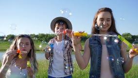 La niñez feliz, las hermanas sonrientes con el pequeño hermano hace burbujas de jabón en césped cerca del lago almacen de video