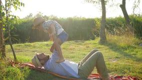 La niñez feliz, los funcionamientos del niño en manos del padre y ellos caen en la manta en luz del sol el verano u otoño del fon almacen de video