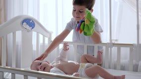 La niñez feliz, muchacho con el juguete a disposición divierte con el bebé en pesebre cerca de ventana almacen de video