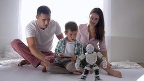 La niñez moderna, niño lindo con los padres juega el robot elegante en teledirigido del teléfono celular que se sienta en piso