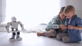 La niñez moderna, niños pequeños aprende controlar el robot humanoid usando un teléfono móvil en casa almacen de metraje de vídeo