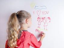 La ni?a dibuja a la familia con el marcador en un tablero blanco imagen de archivo libre de regalías