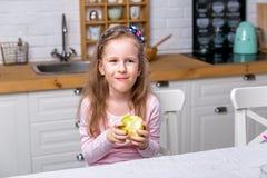 La ni?a feliz desayuna en una cocina blanca Ella come la manzana y la sonrisa Consumici?n sana fotos de archivo