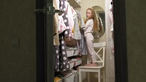 La ni?a hermosa elige el vestido en el guardarropa casero Belleza y moda metrajes