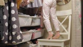 La ni?a hermosa elige el vestido en el guardarropa casero Belleza y moda almacen de metraje de vídeo