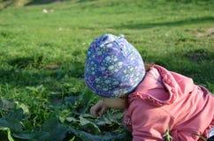 La ni?a juguetona linda sonriente se est? colocando en hierba verde la muchacha que el ni?o camina alrededor del lago aprende cam fotos de archivo