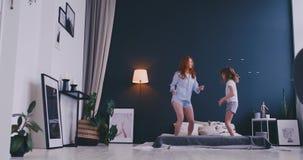 La ni?a linda con su madre cari?osa se divierte que baila el estilo moderno junta que salta y que da el alto cinco en cama almacen de metraje de vídeo