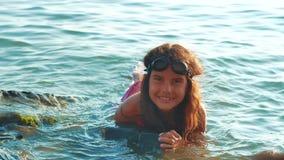 La ni?a se ba?a en el mar con las rocas y las piedras la hija adolescente de la muchacha nada en el agua en la forma de vida de l almacen de video