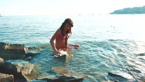 La ni?a se ba?a en el mar con las rocas y las piedras la hija adolescente de la muchacha nada en la forma de vida del agua en las metrajes