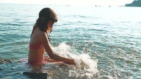 La ni?a se ba?a en el mar con las rocas y las piedras nadadas adolescentes de la forma de vida de la hija de la muchacha en el ag almacen de metraje de vídeo