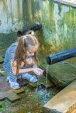 La niña bebe el agua de la fuente Foto de archivo