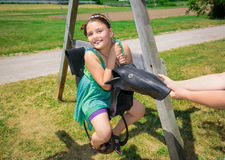 La niña bonita que se sienta en el caucho viejo hecho balancea en parque y disfrutar de su tiempo libre Imagenes de archivo