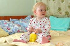 La niña con la botella que introduce se sienta en la cama. Foto de archivo