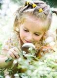 La niña con la lupa mira la flor Imagen de archivo libre de regalías