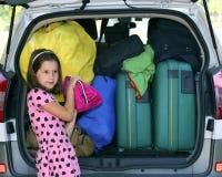 La niña con los corazones viste cargas el coche de equipaje Fotos de archivo