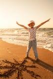 La niña dibuja el sol en la arena en la playa Fotos de archivo