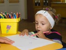 La niña drena el lápiz en el papel Fotografía de archivo