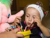 La niña drena el lápiz en el papel Imagen de archivo