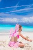 La niña dulce con la mariposa se va volando en la playa blanca Imágenes de archivo libres de regalías