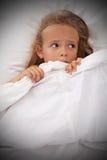 La niña en cama despierta por pesadillas Imagen de archivo