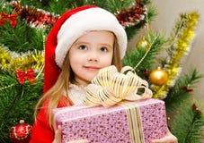 La niña en el sombrero de santa con el presente tiene una Navidad Imagen de archivo libre de regalías
