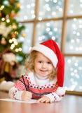 La niña en un sombrero rojo de la Navidad escribe la letra a Santa Claus Imagen de archivo