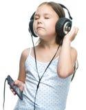 La niña está disfrutando de música usando los auriculares Foto de archivo