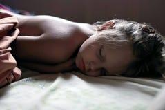 La niña está durmiendo bien en su cama Foto de archivo libre de regalías