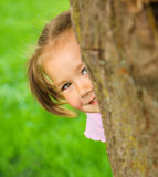 La niña está jugando escondite al aire libre Foto de archivo
