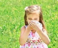 La niña está soplando su nariz en prado verde Fotos de archivo libres de regalías