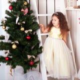 La niña feliz adorna el árbol de navidad. Fotografía de archivo libre de regalías