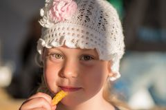 La niña feliz come la patata Fotos de archivo