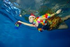 La niña feliz en el sombrero de Santa Claus y el traje para el carnaval flota bajo el agua con un regalo a disposición en fondo a Foto de archivo