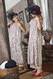 La niña intenta encendido un vestido de las abuelas Fotografía de archivo
