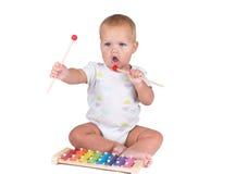 La niña juega el piano, en el fondo blanco Imágenes de archivo libres de regalías
