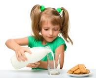 La niña linda está vertiendo la leche en vidrio Imágenes de archivo libres de regalías