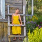 La niña linda se coloca en una escalera de madera en la pared Fotos de archivo