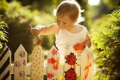 La niña pinta la cerca Foto de archivo libre de regalías