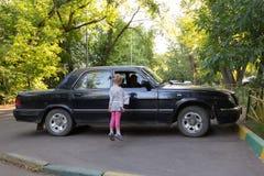 La niña salta a la ventana para ver sentarse en el abuelo del coche Fotografía de archivo