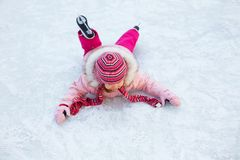 La niña se cayó al patinaje de hielo Foto de archivo libre de regalías