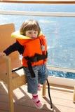 La niña se vistió en soportes del chaleco salvavidas en el balcón de la cabina Fotografía de archivo