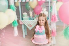 La niña sostiene una torta grande en un cuarto adornado Imagenes de archivo
