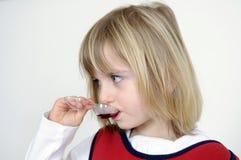 La niña toma la medicina Imagenes de archivo